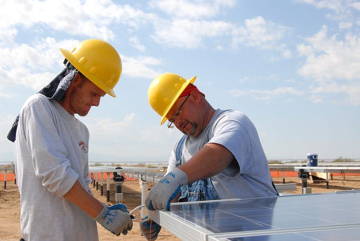 two men installing a 3 phase inverter