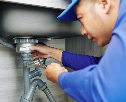 Blocked drains plumber in Canberra repairing the drain in the kitchen