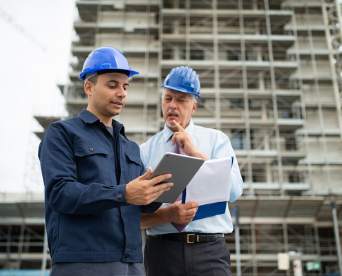 Architect and site manager using a construction project management software in a tablet